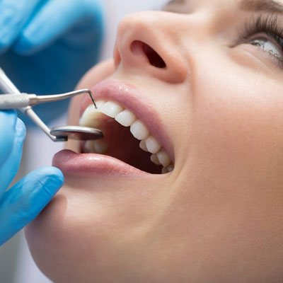 dentist undergoing general dentistry procedure on patient at Vyom - best dental clinic in ahmedabad.