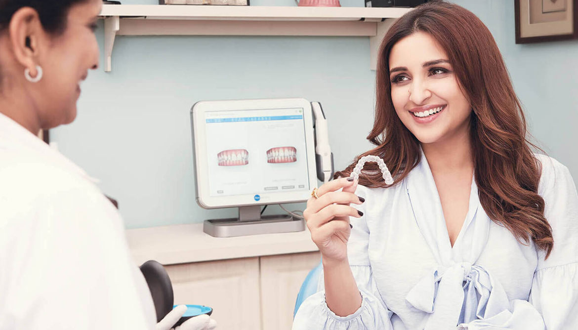 parineeti chopra with dentist displaying the benefits of invisalign. treatment available at vyom dental care ahmedabad